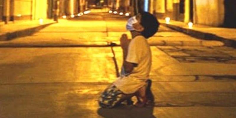 Photo of Fotografa un bambino nel mezzo della notte in ginocchio per strada, mentre prega  Dio